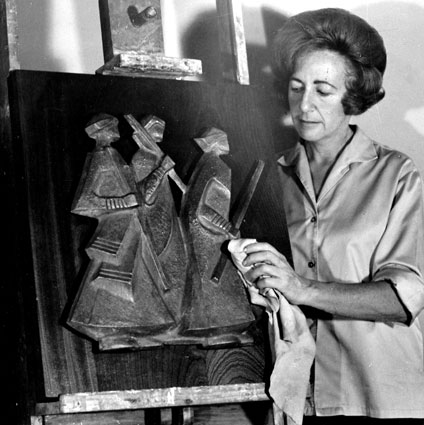 "Lily SACHS applying finishing off touches to her small panel ""Marching Africans"" in bronze on wood"